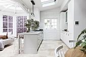 Offene Küche mit hellgrauer, freistehender Theke im Landhausstil in restaurierter Altbauwohnung