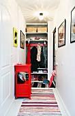 In Wandnische eingebaute Garderobe mit Regalbrettern und Garderobenhakenleiste, davor Flickenteppiche und rotes Ablageschränkchen