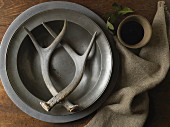 Antlers on pewter plate next to linen cloth