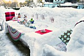 Decorated table sculpted from snow on snow-covered terrace