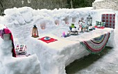 Candles and lanterns arranged on table sculpted from snow on snow-covered terrace