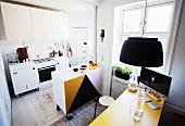 Küche mit halbhohem Schrank auf Rollen und gelber Tischplatte mit Computerbildschirm in Altbauwohnung