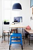 Ess- und Arbeitsplatz vor Fenster in Altbauwohnung; blauer Tritthocker an Tisch unter schwarzer Pendelleuchte
