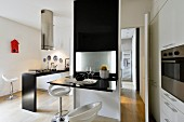 White bar stools in front of black partition with fold-up, glossy table top