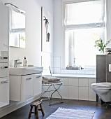 Weisses Bad mit eingebauter Badewanne vor dem Fenster