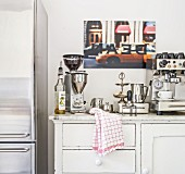 Coffee mill and espresso machine on top of vintage kitchen dresser with marble top