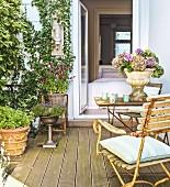 Romantische Terrasse mit Vintage Gartentisch, Stühlen und bepflanzten Blumengefäßen