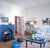 Blue-tiled open fireplace in Scandinavian living room