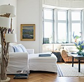 White chaise sofa and driftwood standard lamp in living area with wicker sofa in window bay in background