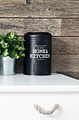 Black metal tin and foliage plant on kitchen cabinet against rustic wood cladding