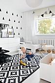 Schwarz-weiss gestaltetes Kinderzimmer mit spielendem Jungen auf Teppich