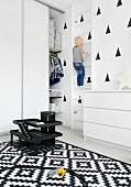 Kind beim Klettern an Sprossenwand in schwarz-weiss gestaltetem Kinderzimmer