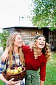 Smiling women in garden holding basket of freshly picked apples