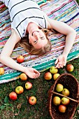 Woman lying on rug with basket of freshly picked apples outdoors