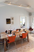 Autumnally set dining table and orange chairs