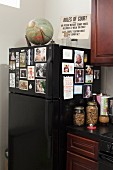 Globe and sign on top of black fridge decorated with photos in corner of kitchen