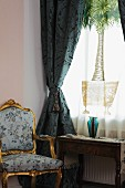 Baroque armchair next to window with heavy blue curtains and printed voile