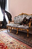 Baroque sofa on various rugs next to stuffed peacock