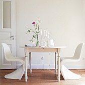 Glass vase and candelabra on wooden table with classic white chairs