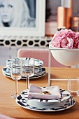 Black and white place setting with cloth napkin and bowl with pink flowers on dining table