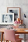 Schale mit rosa Blüten auf Esstisch vor schwarz-weißem Konsolentisch mit gerahmten Bildern