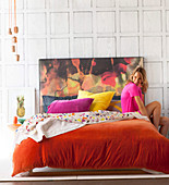 Young woman on double bed with orange velvet cover and colorful headboard