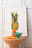 Cork side table with ceramic bowls and vase in front of picture with pineapple motif