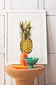 Kork-Beistelltisch mit Keramikschalen und Vase vor Bild mit Ananasmotiv