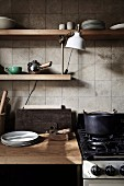 Kitchenette with wooden worktop and wall shelves in front of tiled wall, gas stove next to it