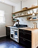 Black kitchenettes with wooden worktops and suspended wall shelves in front of wall tiles
