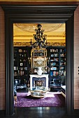 Library with open fire and gilt-framed mirror in historical interior