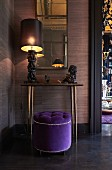 Elegant purple pouffe in front of artistic table lamp and animal ornament on console table