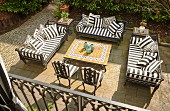 View down onto terrace with black and white striped cushions on outdoor furniture