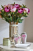 Vase of peonies and glass ornaments on side table in front of patterned wallpaper