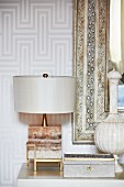 Table lamp, jewellery box and vase in front of mirror with antique frame