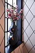 Branches of pink flowers in black vase in front of lattice window