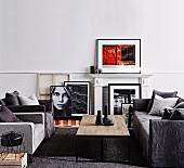 Sofa set in shades of gray and coffee table with rustic table top, white fireplace cladding and framed photo art