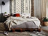 Doppelbett auf rustikalen Paletten vor weißer Ziegelwand mit Wandteppich