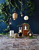 Hanging lamps in front of a wall painted dark blue, various lanterns with burning candles on tiled floors