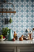 Kitchenette in front of blue and white pattern wallpaper