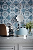 Retro teakettle and toaster on kitchen counter in front of blue and white wallpaper