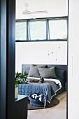 Blick durch offene Schlafzimmertür auf Bett mit Tagesdecke und liegender Katze
