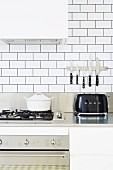 White tiled kitchen with stainless steel worktop, gas stove and black toaster under magnetic bar for knives