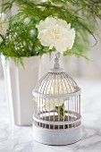 White carnation in vintage-style birdcage ornament in front of vase of carnations on marble surface