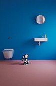 Toilet and sink on blue wall and toy robot on mauve floor in minimalist bathroom