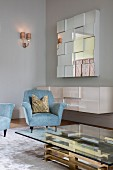 Glass coffee table with brass base, light blue armchairs and floating sideboard below mirrored wall-mounted cabinet