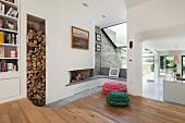 Moderner Wohnbereich mit Holzboden, vor Kaminecke farbige Sitzpoufs und Durchgang mit Blick in offene Küche