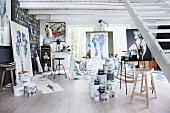 Pots of paint, desk and artworks in painter's studio
