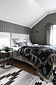 Ethnic bedspread on double bed against wooden wall painted dark grey