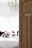 Name on open interior door, soft toys on bed and white chandelier